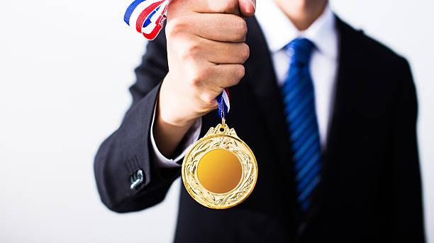 businessman holding gold medals - foto de stock