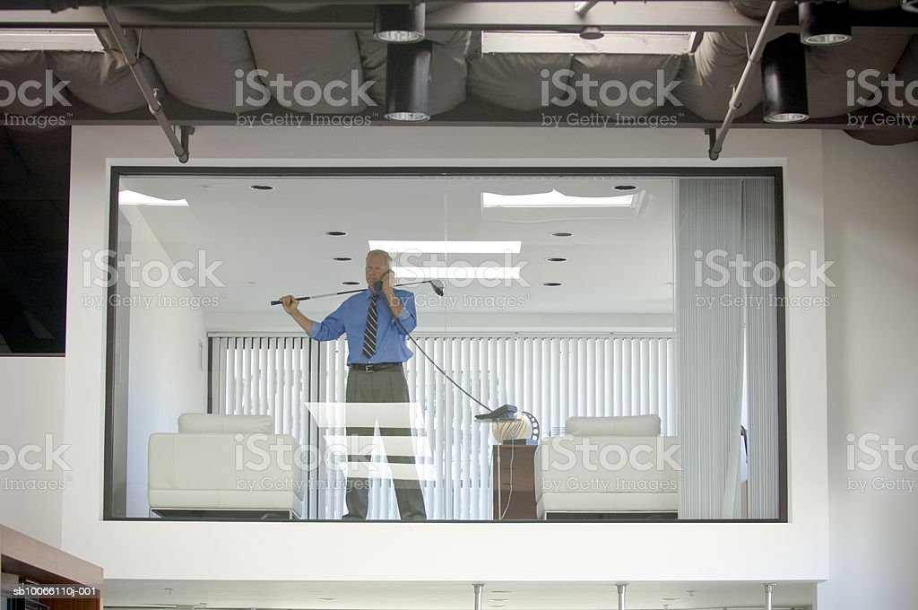 Businessman holding golf in office, using landline phone royalty-free stock photo