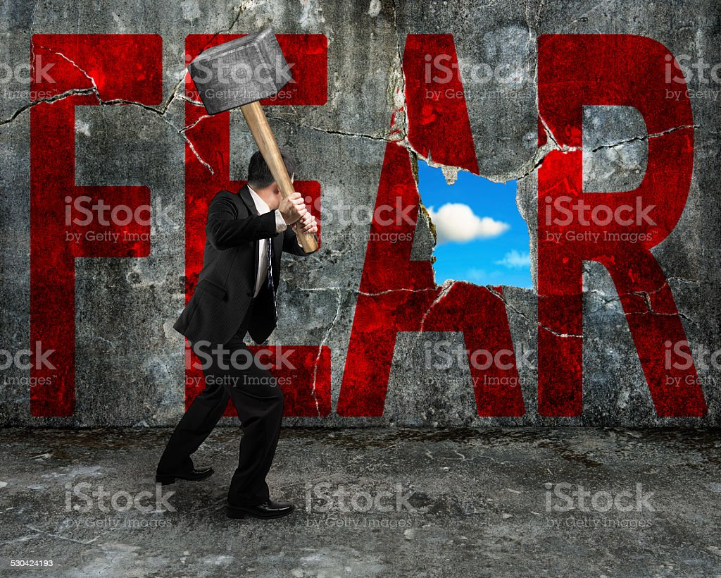 businessman holding hammer hitting red FEAR word on concrete wall...