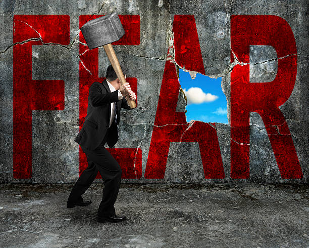 businessman holding hammer hitting red FEAR word on concrete wal stock photo