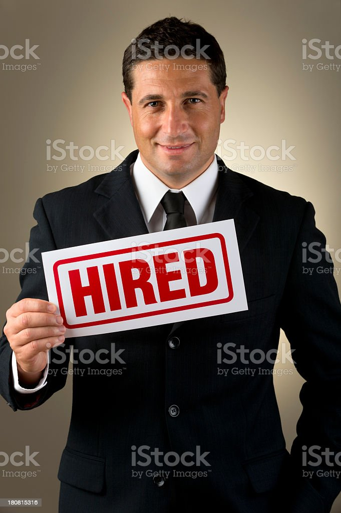 Businessman holding hired sign. stock photo