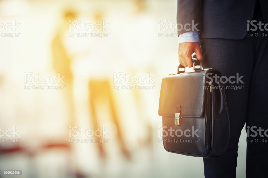 businessman holding his briefcase in office - foto stock