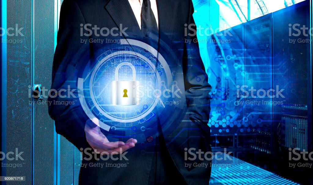 businessman holding hologram with the concept of data protection against the background of supercomputer data center stock photo
