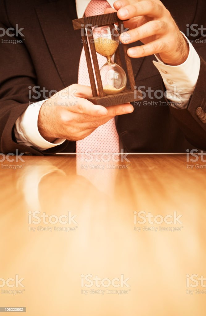 Businessman Holding Hourglass and Sitting at Desk royalty-free stock photo