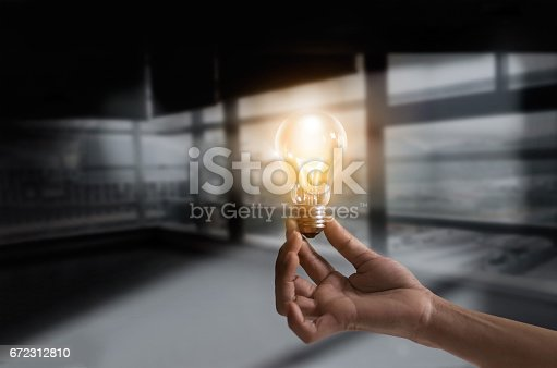 istock Businessman holding illuminated light bulb concept for idea, innovation and creativity inspiration concept ideas 672312810