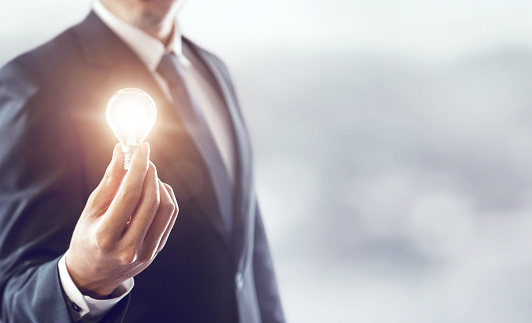 istock Businessman holding illuminated light bulb, idea, innovation and inspiration concept, background for copy. 850621354