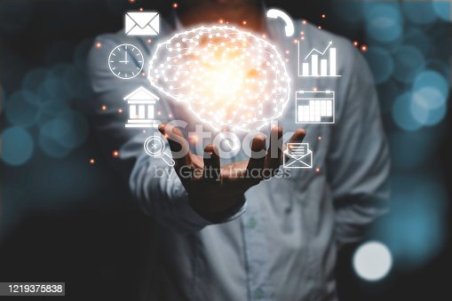 881350654 istock photo Businessman holding illustration brain and other infographic such as graph telephone calendar e-mail clock with bokeh background. Brain is centralise to control creativity  idea memory and psychology. 1219375838