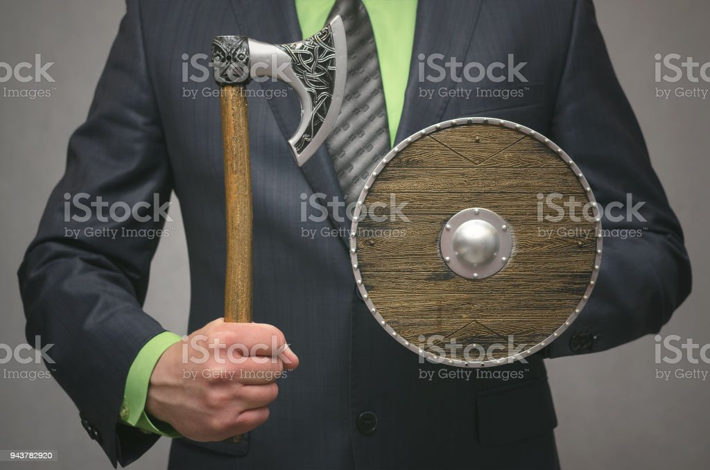 Businessman holding in hands a toy viking axe and shield. Security agent. Sentinel. Protection of deposits stock photo