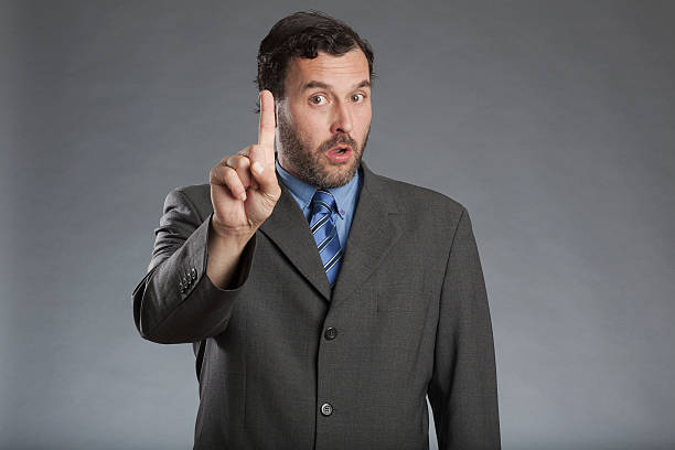 businessman holding index finger up against gray background - stay tuned bildbanksfoton och bilder