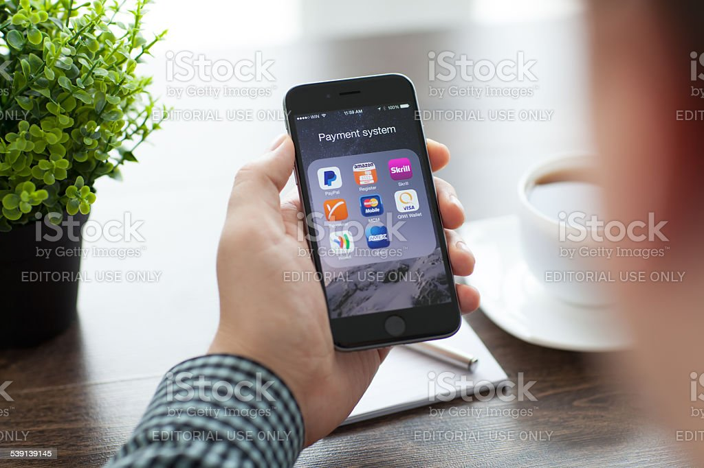 Businessman holding iPhone 6 with a set of payment system stock photo