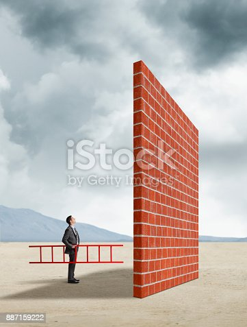 A businessman stands while holding a red ladder as he looks up at a brick wall that he is thinking of climbing