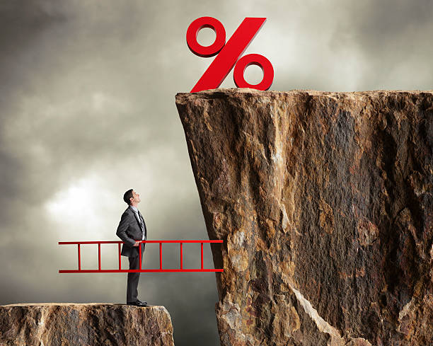 businessman holding ladder staring up at higher interest rates - interest rate stock photos and pictures