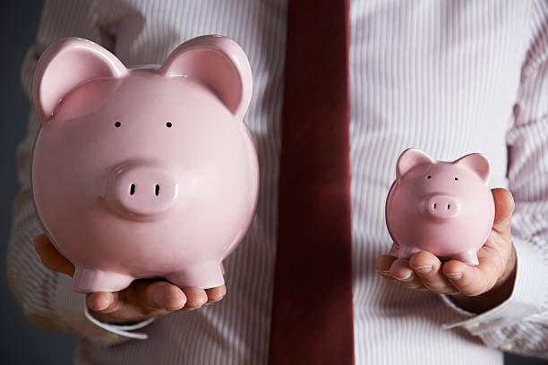 Businessman Holding Large And Small Piggy Bank stock photo