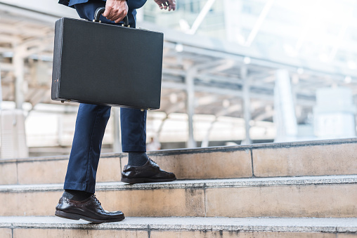 684803840 istock photo businessman holding leather briefcase while walking 648284552