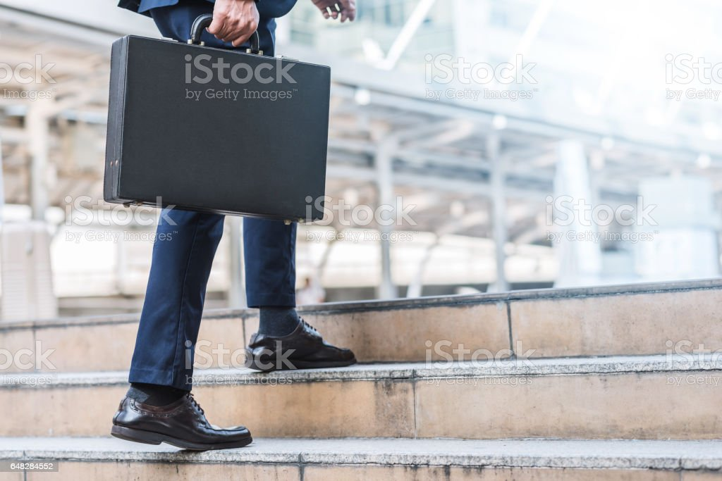 businessman holding leather briefcase while walking stock photo