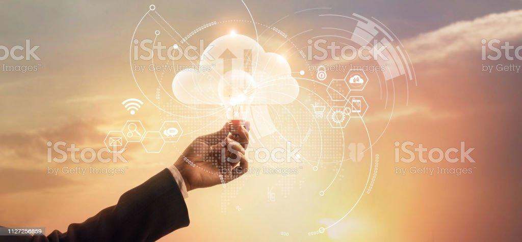 実業家持株電球。技術革新とネットワーク接続、クラウドコンピューティング技術のシンボルです。ビジネス戦略と開発。分析データは、夕日を背景に経済成長。 ロイヤリティフリーストックフォト