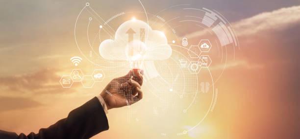 i̇şadamı holding ampul. yenilik ve ağ bağlantı, bulut bilgisayar teknolojisi sembolü. i̇ş stratejisi ve geliştirme. veri ve ekonomik büyüme günbatımı arka plan üzerinde analiz. - bulut bilişimi stok fotoğraflar ve resimler