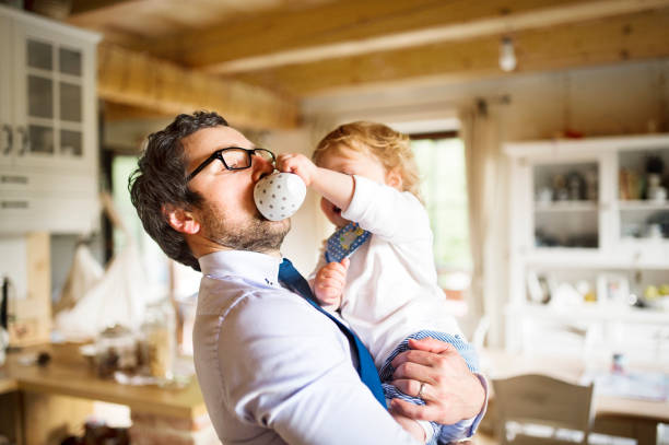 Businessman holding little son in the arms, drinking coffee. stock photo