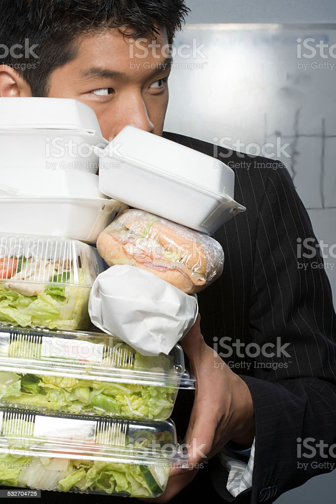 Businessman holding lots of food stock photo