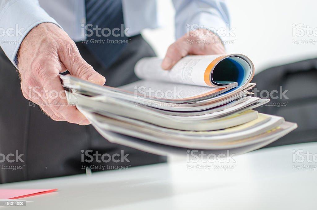 Businessman holding magazines stock photo