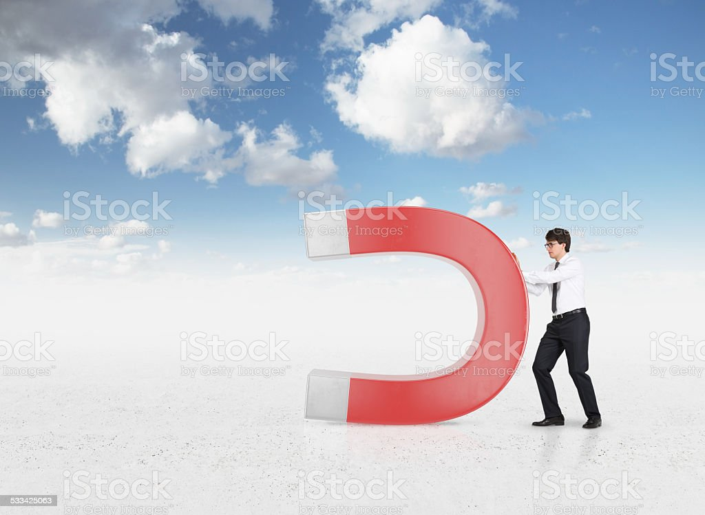 businessman holding magnet stock photo