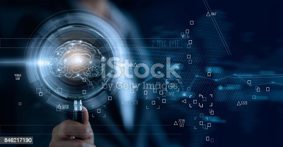 istock Businessman holding magnifying glass and digital brain, searching of a teamwork brainstrom for effective business 846217190