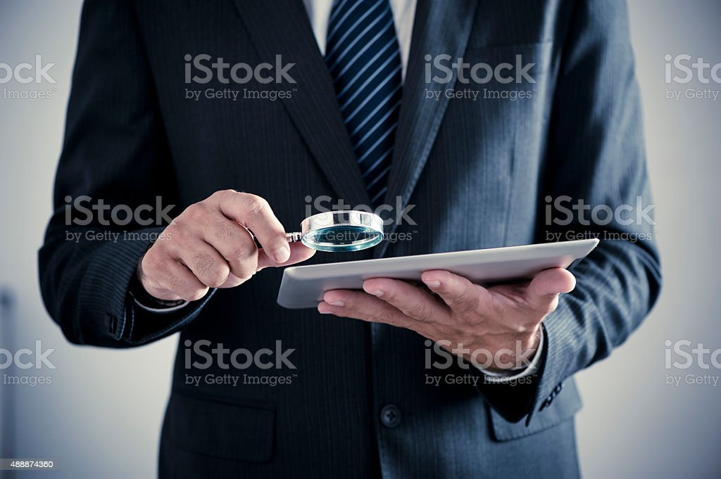 Businessman holding magnifying glass and digital tablet stock photo
