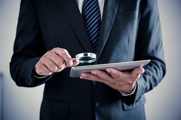 geschäftsmann holding lupe und tablet pc - fehler problem stock-fotos und bilder
