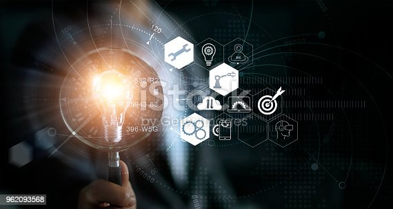 istock Businessman holding magnifying glass and light bulb. Idea and imagination. Creative and inspiration. Innovation icon network connection. Search engine optimisation. Innovative technology in science and industrial concept 962093568
