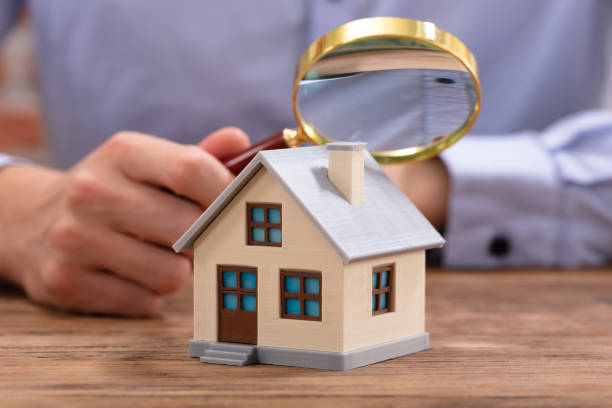 businessman holding magnifying glass over house model - esaminare foto e immagini stock