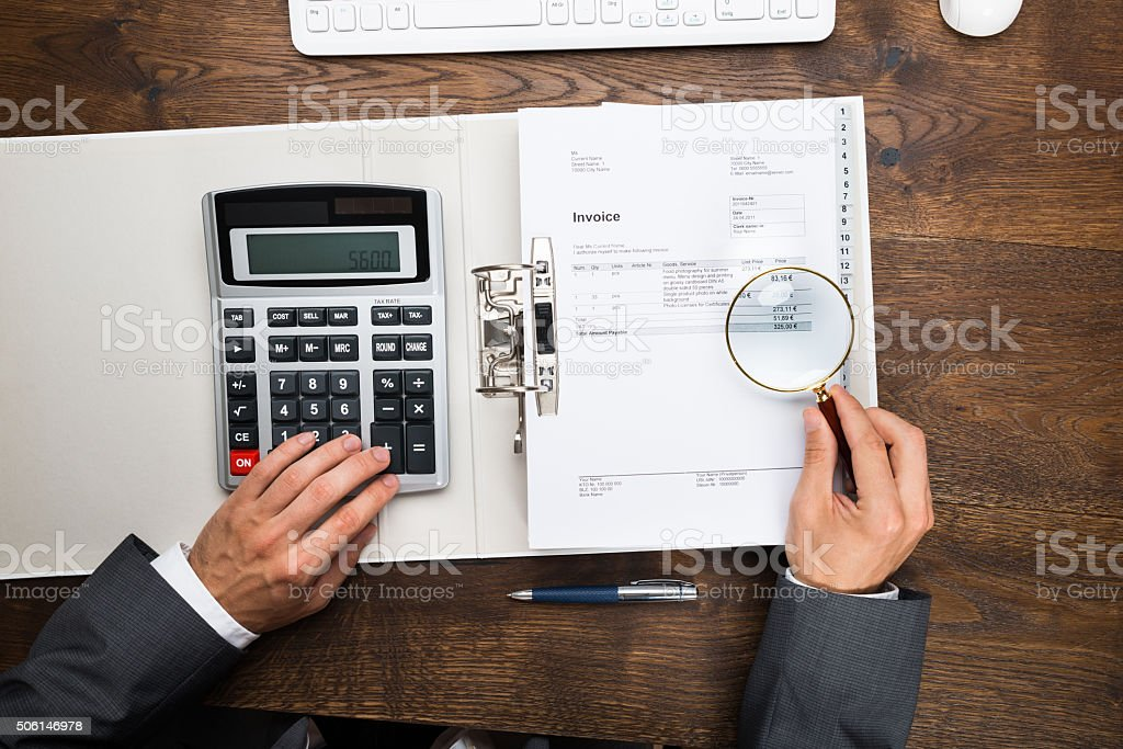 Businessman Holding Magnifying Glass Over Invoice stock photo