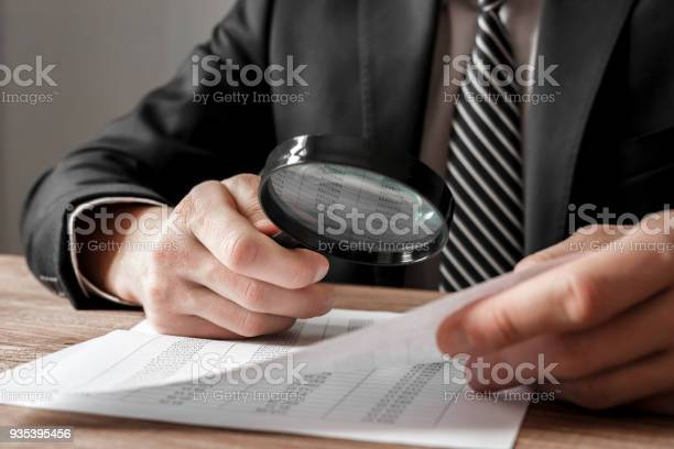 Businessman holding magnifying glass zoom and analyzing financial picture id935395456?b=1&k=6&m=935395456&s=612x612&h= ro t 3ajwzoxh4xs6mrhwqdra waa sdzdk6e9qvn0=