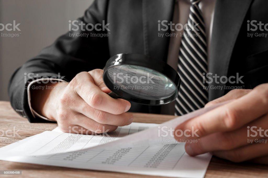 Geschäftsmann hält Lupe Zoom und Analyse von Finanzkennzahlen – Foto