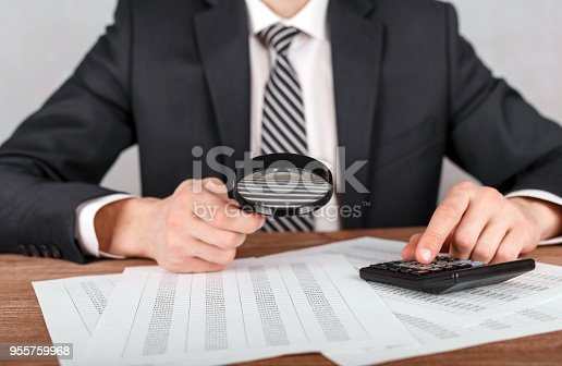 istock Businessman holding magnifying glass zoom and looking to financial statement 955759968