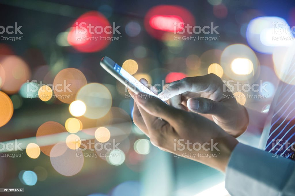 Businessman holding mobile phone at night street stock photo