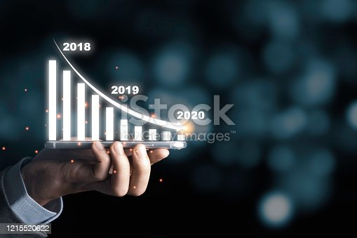 Businessman holding mobile phone with infographic graph and arrow down trend in 2020 economic crisis.It is symbol of business investment down from trade war and coronavirus (COVID 19).