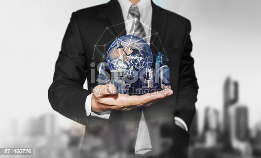 684793898 istock photo Businessman holding modern buildings with global network connection. Elements of this image are furnished by NASA 871460726