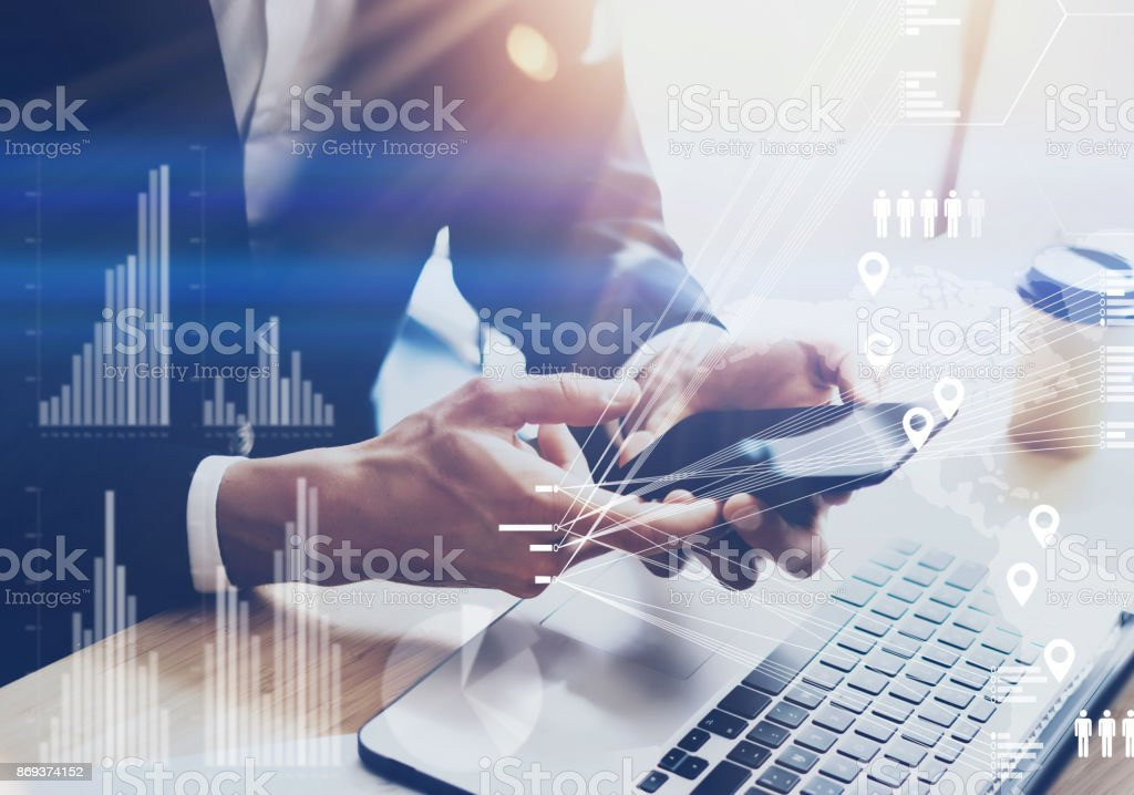 Businessman holding modern smartphone on hands.Concept of digital diagram,graph interfaces,virtual screen,connections icon.Blurred background. stock photo
