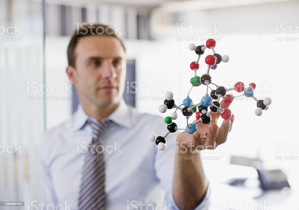 Businessman holding molecule model in office royalty-free stock photo