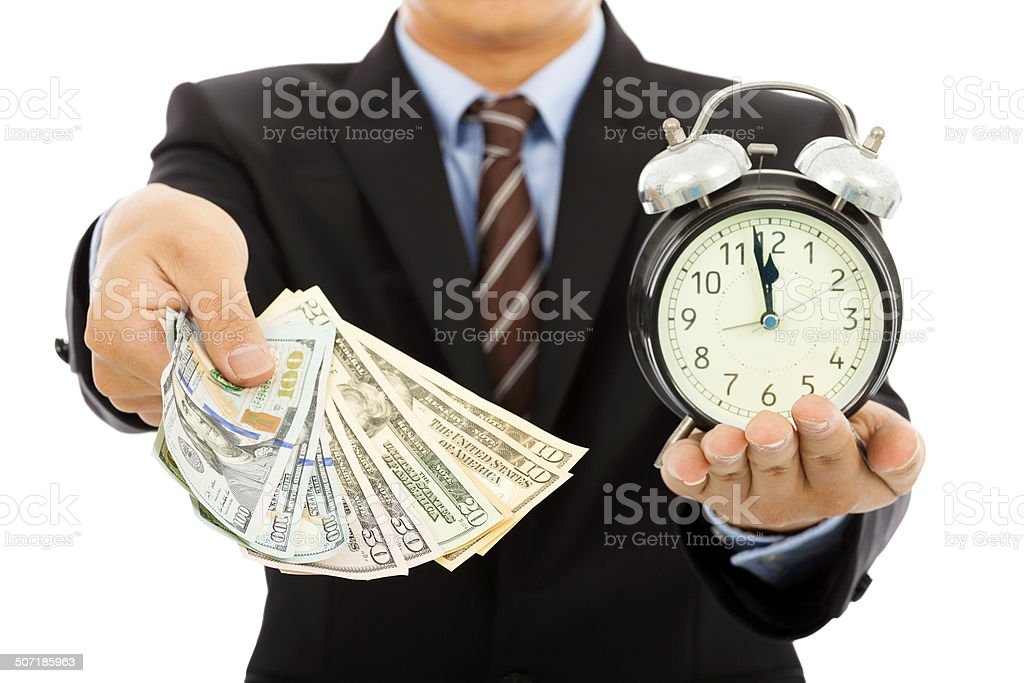 businessman holding money and clock. time is money concept in studio