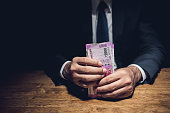 istock Businessman holding money, Indian Rupee currency, at the table in dark room 982985564