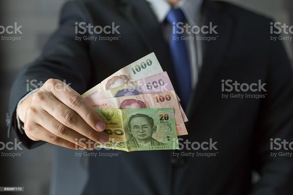 Businessman holding money thai baht stock photo