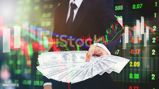 istock Businessman Holding money US dollar bills on digital stock market financial exchange information and Trading graph background 889225914
