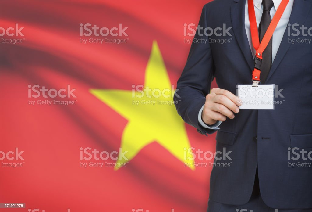 Businessman holding name card badge on a lanyard with a national flag on background - Vietnam royalty-free stock photo
