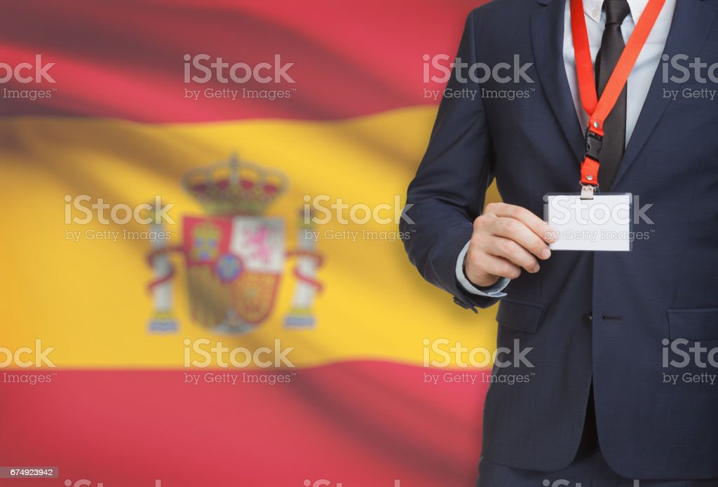 Businessman holding name card badge on a lanyard with a national flag on background - Spain royalty-free stock photo