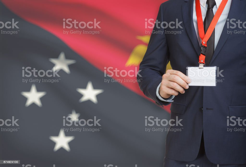 Businessman holding name card badge on a lanyard with a national flag on background - Papua New Guinea royalty-free stock photo