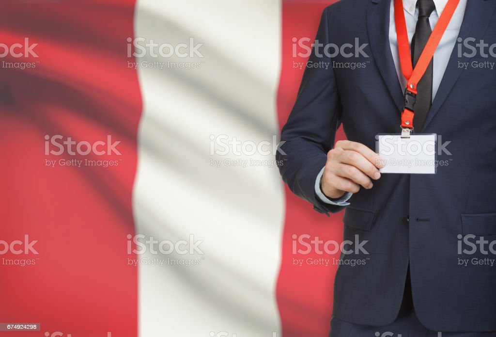 Businessman holding name card badge on a lanyard with a national flag on background - Peru royalty-free stock photo