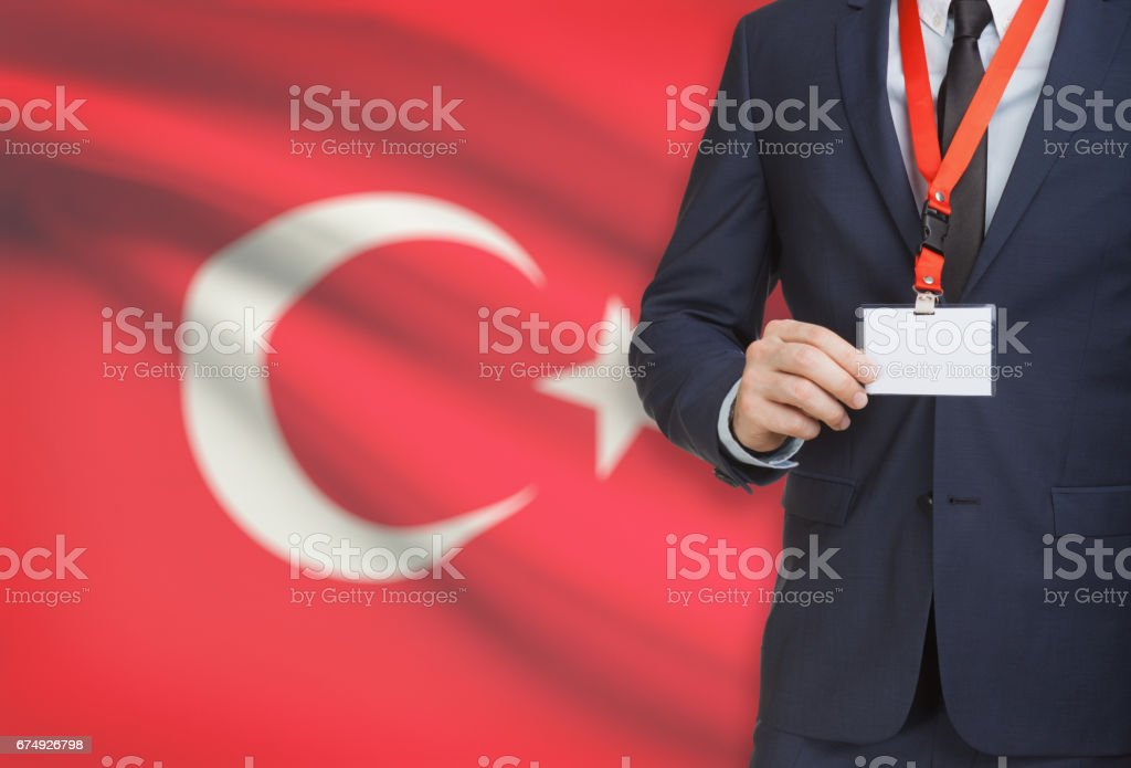 Businessman holding name card badge on a lanyard with a national flag on background - Turkey royalty-free stock photo