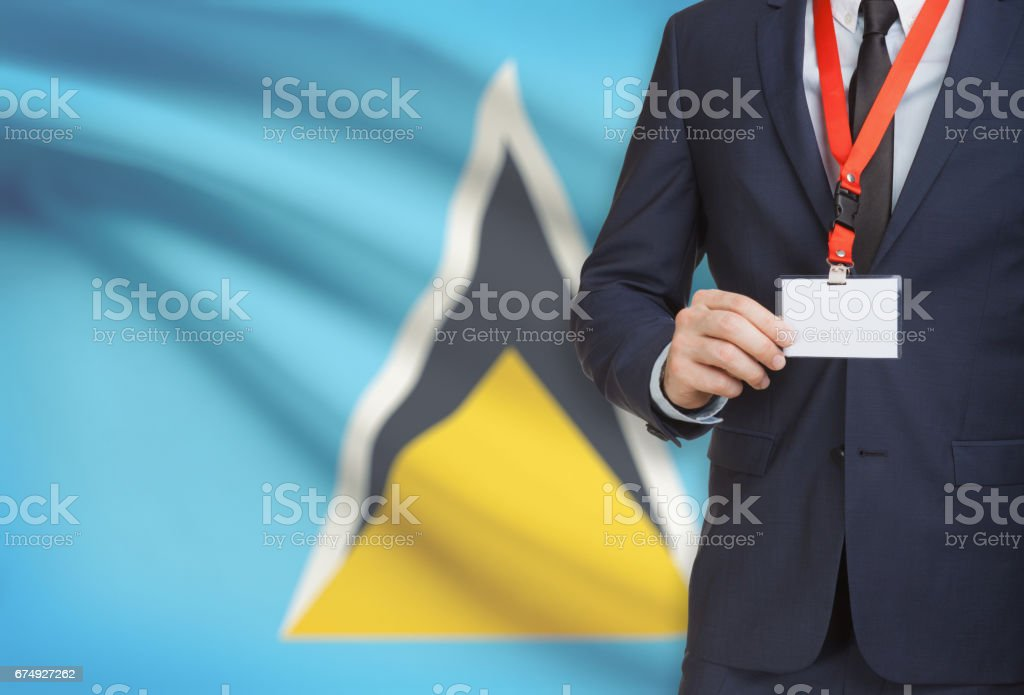 Businessman holding name card badge on a lanyard with a national flag on background - Saint Lucia royalty-free stock photo