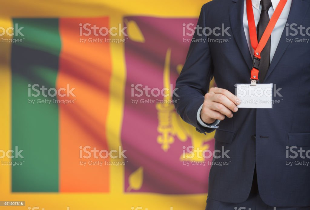 Businessman holding name card badge on a lanyard with a national flag on background - Sri Lanka royalty-free stock photo